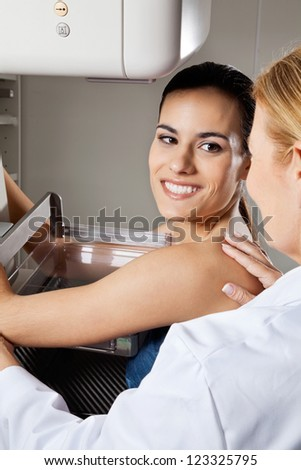 Happy young female patient looking at doctor while undergoing mammogram x-ray test