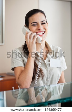 Happy young female receptionist answering phone call