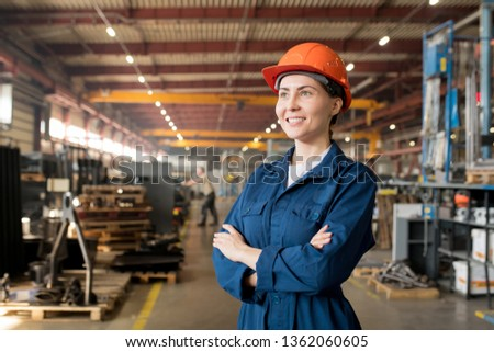 Happy young female technician in blue workwear and helmet standing inside large workshop in factory