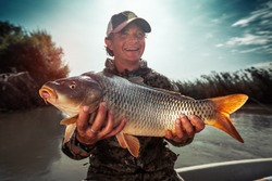Happy young fisherman holds the big Carp fish (Cyprinus carpio) and smiles