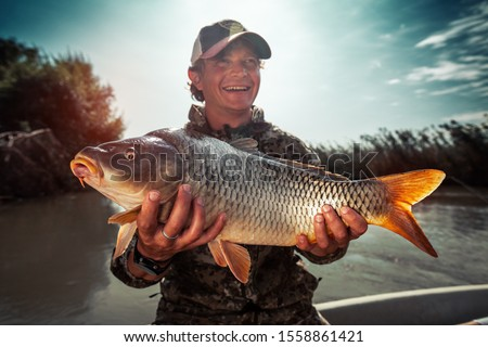 Happy young fisherman holds the big Carp fish (Cyprinus carpio) and smiles