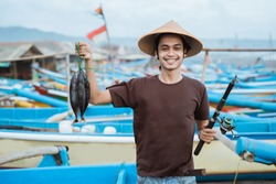 Happy young fisherman on the beach holding his catch fish and shows in front of his boat