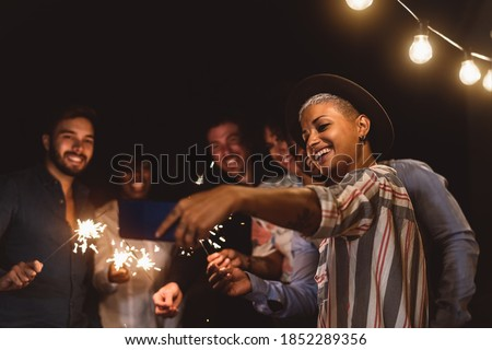 Happy young friends celebrating new year eve with sparklers fireworks while taking selfie with mobile smartphone on patio house party - Youth people lifestyle and holidays concept