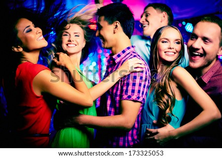 Happy young friends dancing in the nightclub