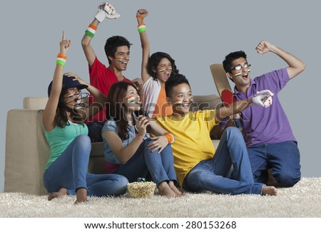 Happy young friends having a great time together while watching cricket match at home