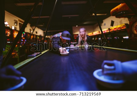 Happy young friends playing air hockey game at amusement park. Man hitting puck with striker.