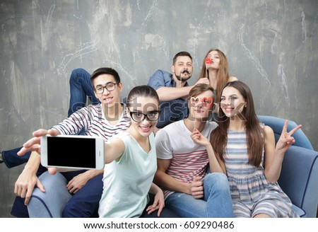 Happy young friends taking selfie while sitting on sofa near grunge wall #609290486