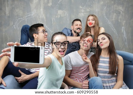 Happy young friends taking selfie while sitting on sofa near grunge wall #609290558