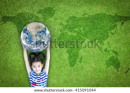 Happy young girl child kid raising blue marble planet earth grass ground lawn nature background: World sustainable environment CSR ESG eco bio friendly concept: Element of the image furnished by NASA