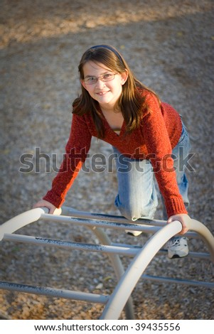 Happy young girl climbing on playground