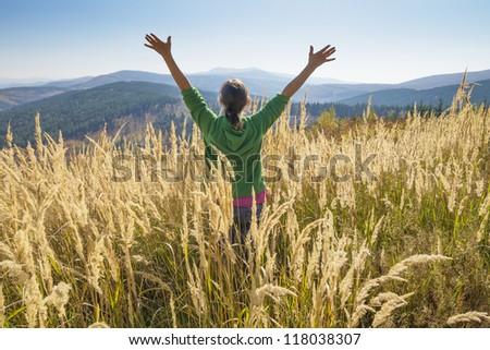 Happy young girl enjoying the beauty of sunny autumn day high in the mountains