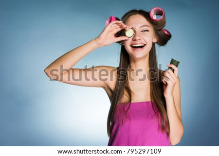 happy young girl holding a cucumber for moisturizing the skin of the face, on the head of curlers #795297109