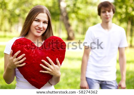 happy young girl holding big red heart, young man in background