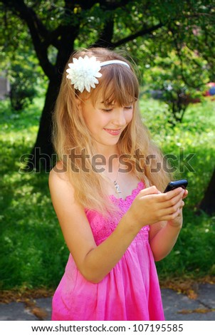 happy young girl holding mobile phone standing in park