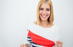 Happy young girl holding Polish flag over gray background and looking at camera