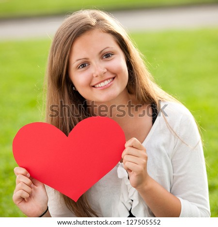 Happy young girl holding red heart on Valentine's Day