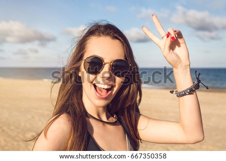Happy young girl in sunglasses showing peace gesture and looking at camera while standing on a seashore