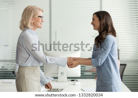 Happy young girl intern student worker get appreciated promoted hired rewarded handshaking helpful female old boss teacher, businesswomen handshake in office as gratitude recognition thanks concept