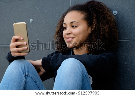Happy young girl looking her mobile phone #512597905