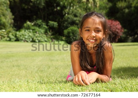 Happy young girl lying on grass in park sunshine