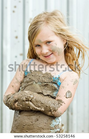 happy young girl playing in the mud