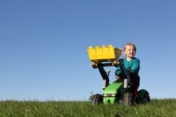 Happy young girl plays on a toy tractor outdoors in the garden