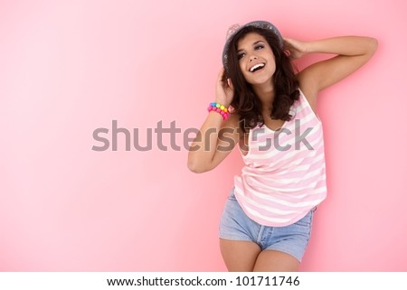 Happy young girl posing in hat over pink wall.
