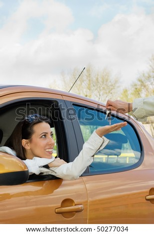 Happy  young girl sitting in a new car and getting a car keys