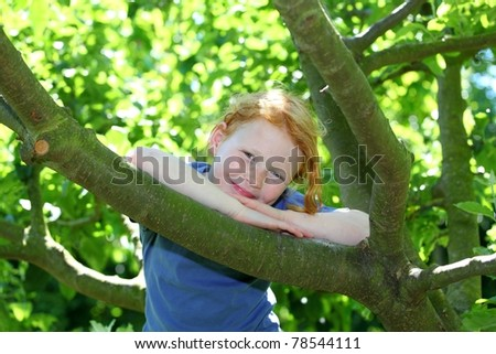 Happy young girl sitting in a tree #78544111