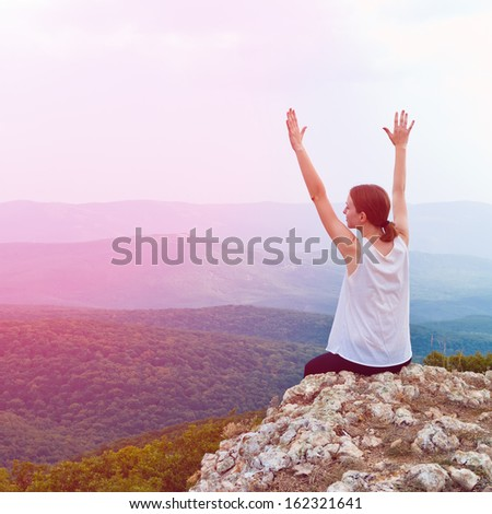 Happy young girl sitting on a cliff side. Young woman relaxing in mountains at sunrise