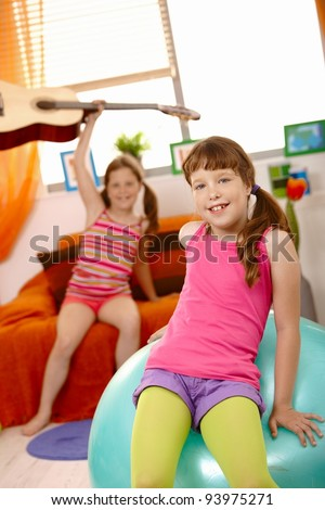 Happy young girl sitting on gym ball, smiling at camera, friend in background raising guitar.? #93975271
