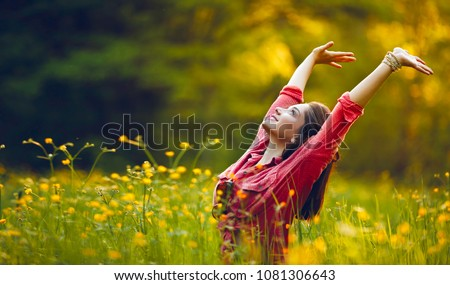 Happy young girl smiling with arms raised outdoor. Freedom and praying concept.