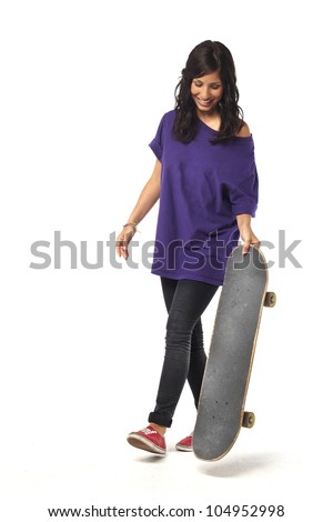 Happy young girl walking with skateboard against isolated background
