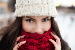 Happy young girl warming up in warm winter clothes.Smiling young woman cover her face with big red scarf.Attractive brunette model portrait outdoor in cold day.Freezing female outside