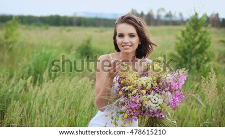 Happy young girl with a bouquet of wild flowers in his hand. Summer day in blossoming fields.