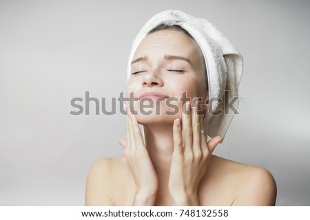 happy young girl with clean skin and with a white towel on her head washes face #748132558