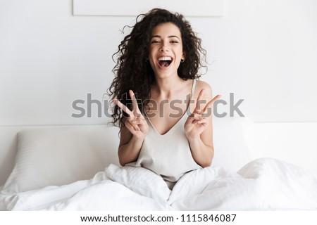Happy young girl with dark curly hair sitting in bed in the morning and showing peace gesture