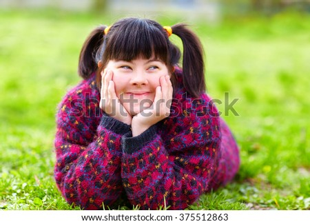 happy young girl with disability on spring lawn #375512863