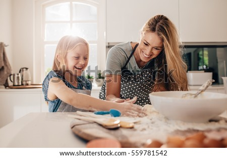 Happy young girl with her mother making dough. Mother and daughter baking in kitchen. #559781542