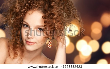 Happy young girl with long and shiny curly hair.  Beautiful model woman