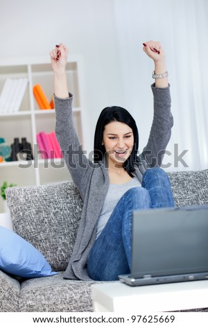 Happy young girl with raised arms sitting in bright living room and smiling, she has a laptop front her