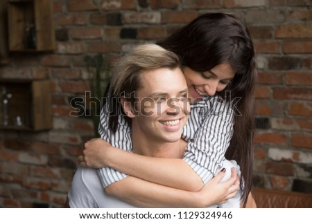 Happy young girlfriend piggyback smiling boyfriend, enjoying spending time together having fun at home, loving wife hugging husband, showing support and affection. Relationship concept #1129324946