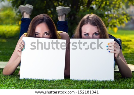 Happy young girls holding white blank papers against background of summer green park. Young girls showing blank boards. Female models portrait outside.