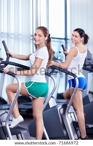 Happy young girls in the fitness club
