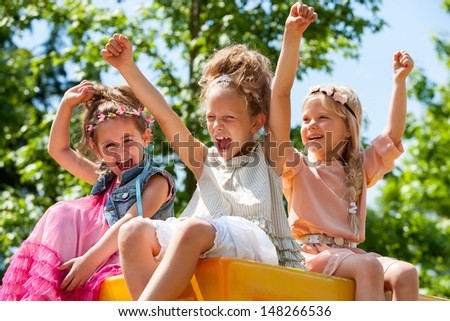 happy young girls raising hands together in park.