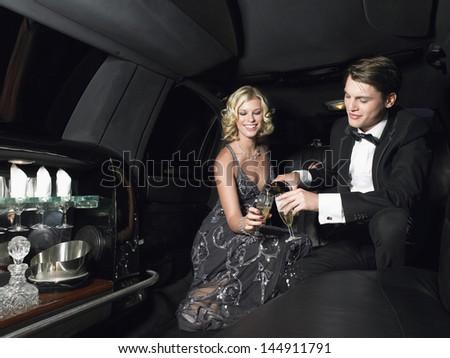 Happy young glamorous couple enjoying champagne in limousine