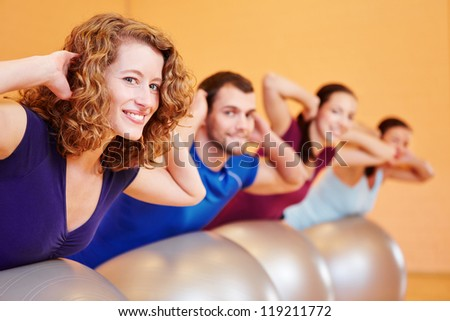 Happy young group doing fitness exercises in health club