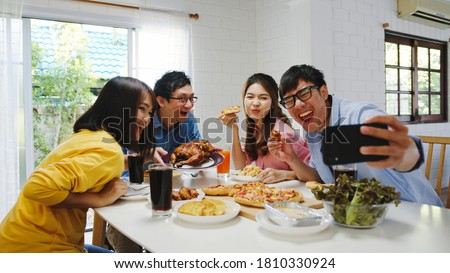 Happy young group having lunch at home. Asia family party eating pizza food and making selfie with her friends at birthday party at dining table together at house. Celebration holiday and togetherness
