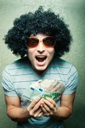 Happy young guy in afro curly wig with eyeglasses holding lots of money