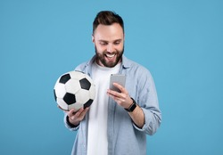 Happy young guy with soccer ball using smartphone, winning sports bet, rooting for his favorite team on blue background